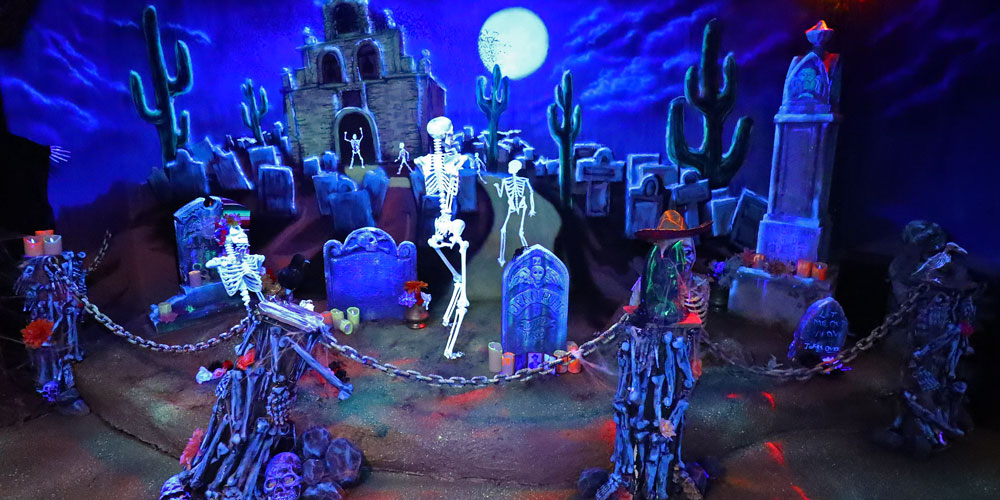 Skeletons and gravestones under a full moon in the Boo Hill Cemetery area inside the Frightful Frontier Haunted House at The Children's Museum of Indianapolis.