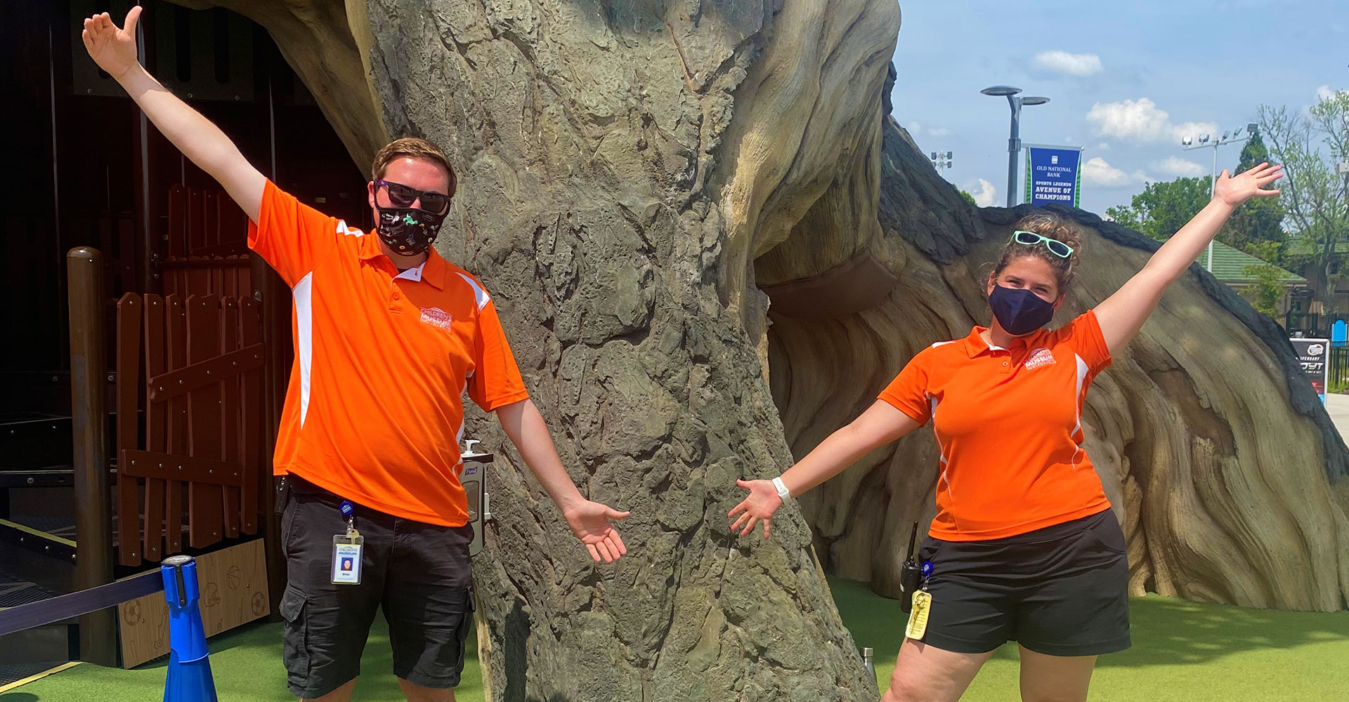 Riley Children's Health Sports Legends Experience coaches Brian and Elizabeth in front of the Tree of Sports at The Children's Museum of Indianapolis